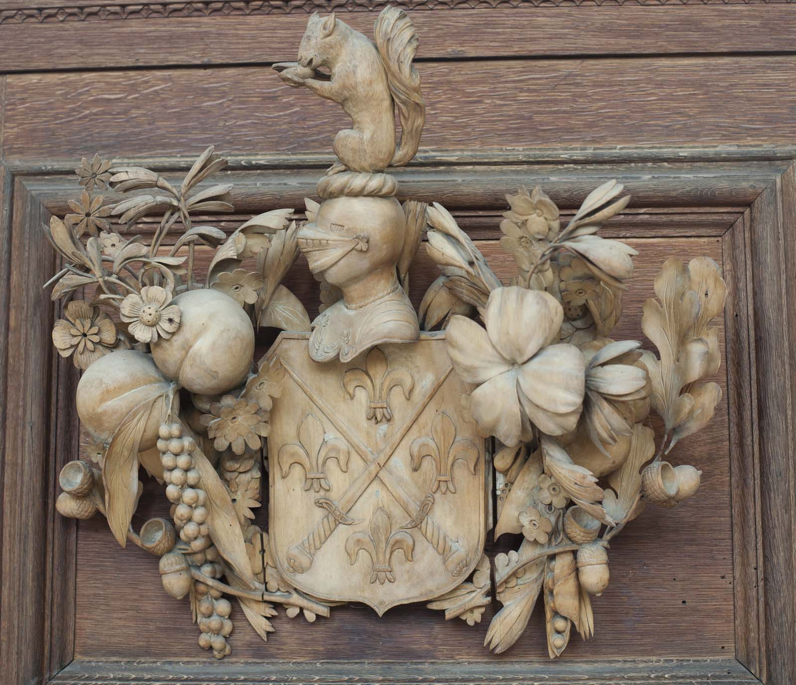 a coat of arms carved in wood with shield, knights helmet, foliage and a squirrel