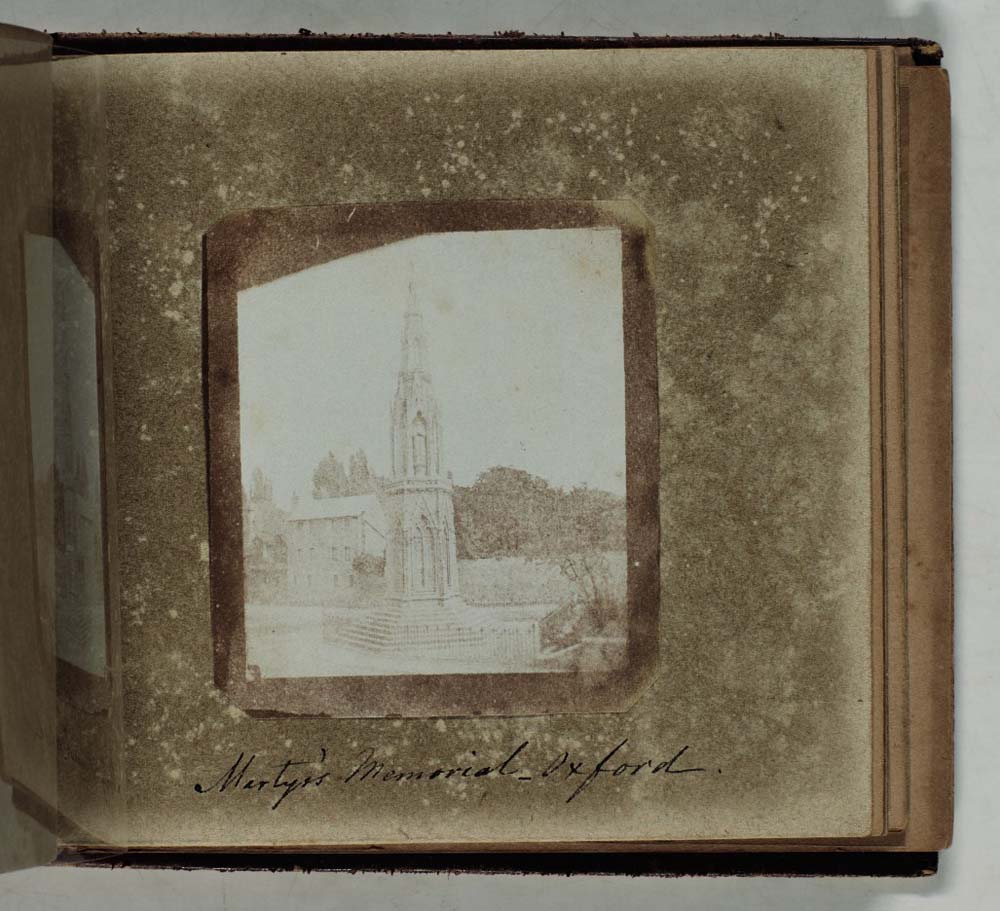 photo of a open page of an photo album with a sepia toned photo of an spired monument