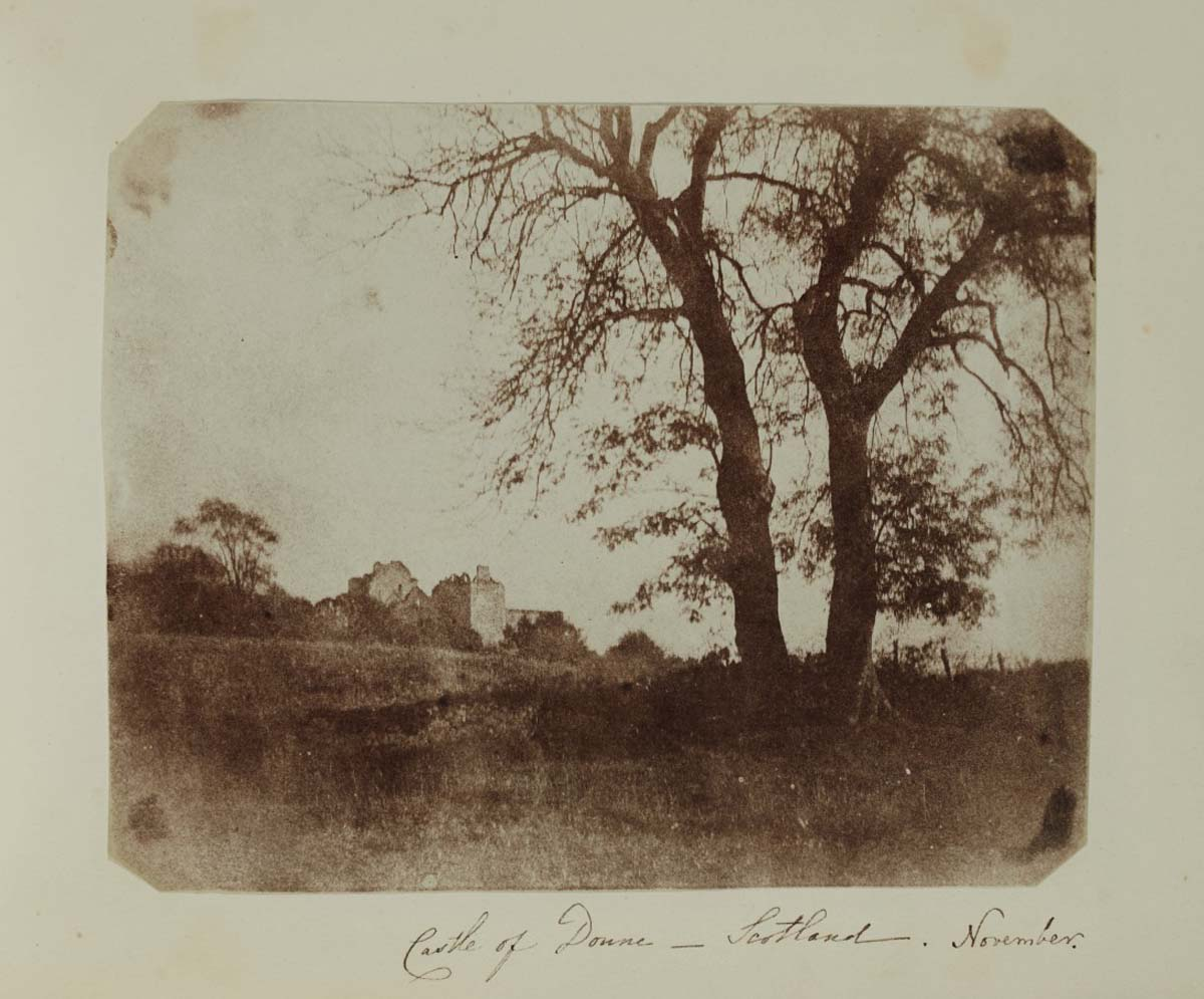 black and white photo of a ruined castle see beyond trees