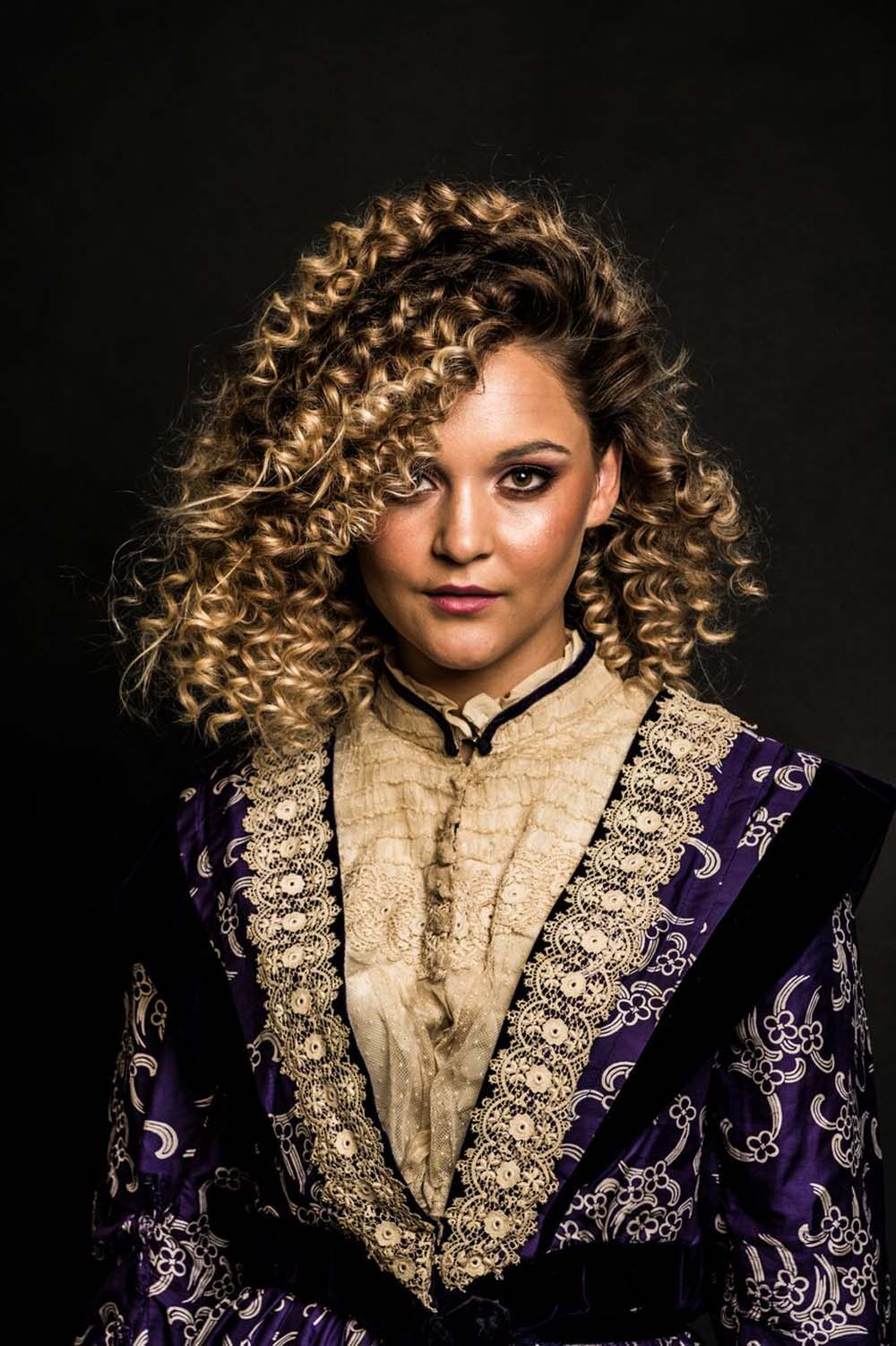 photo of a model with curly hair wearing a Victorian dress
