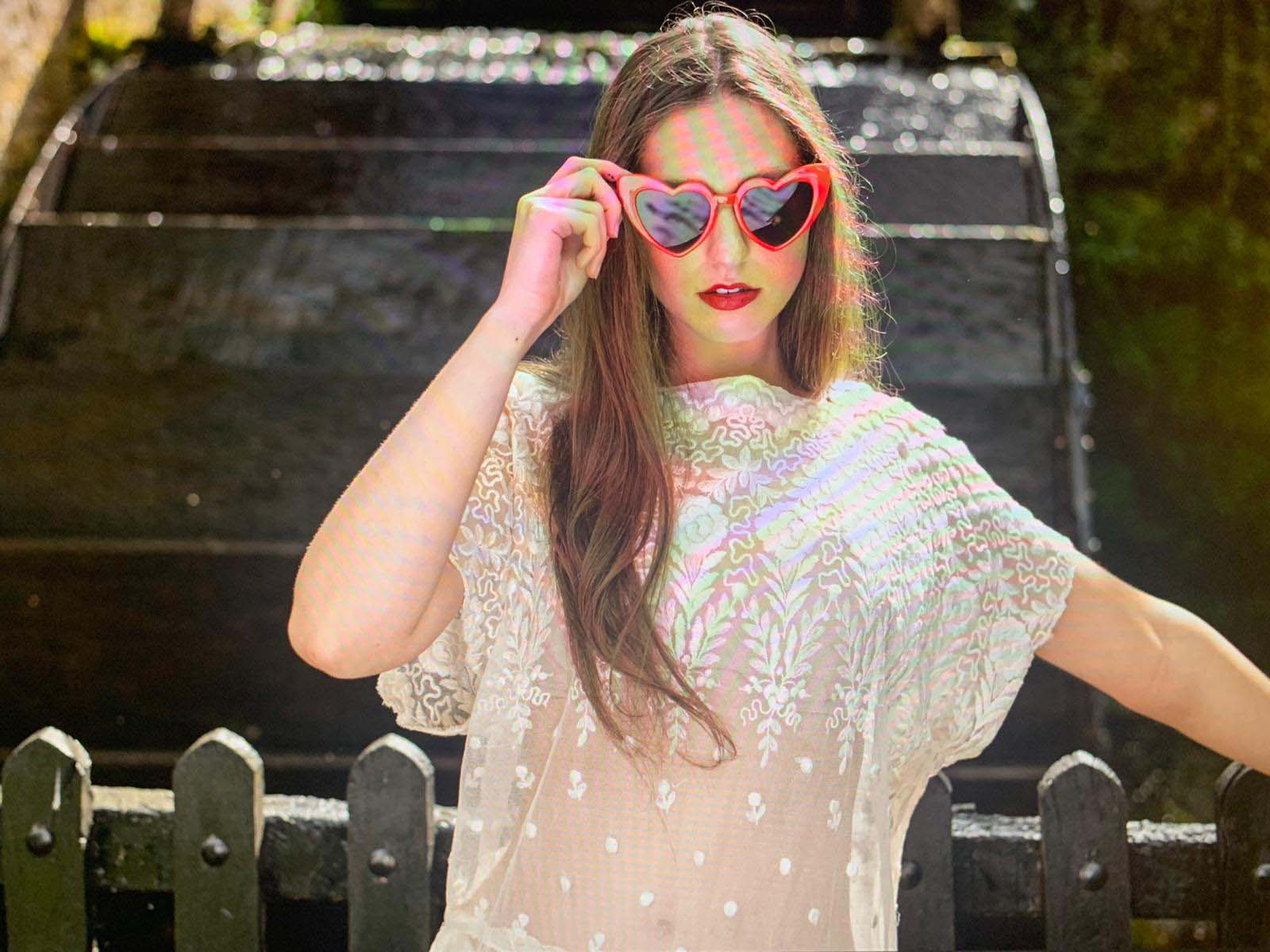 photo of a model with lng hair and heart shaped sunglasses wearing a lace dress