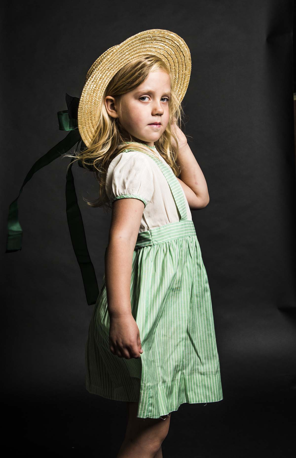 photo of a young girlwearing a straw hat and green dress and white blouse