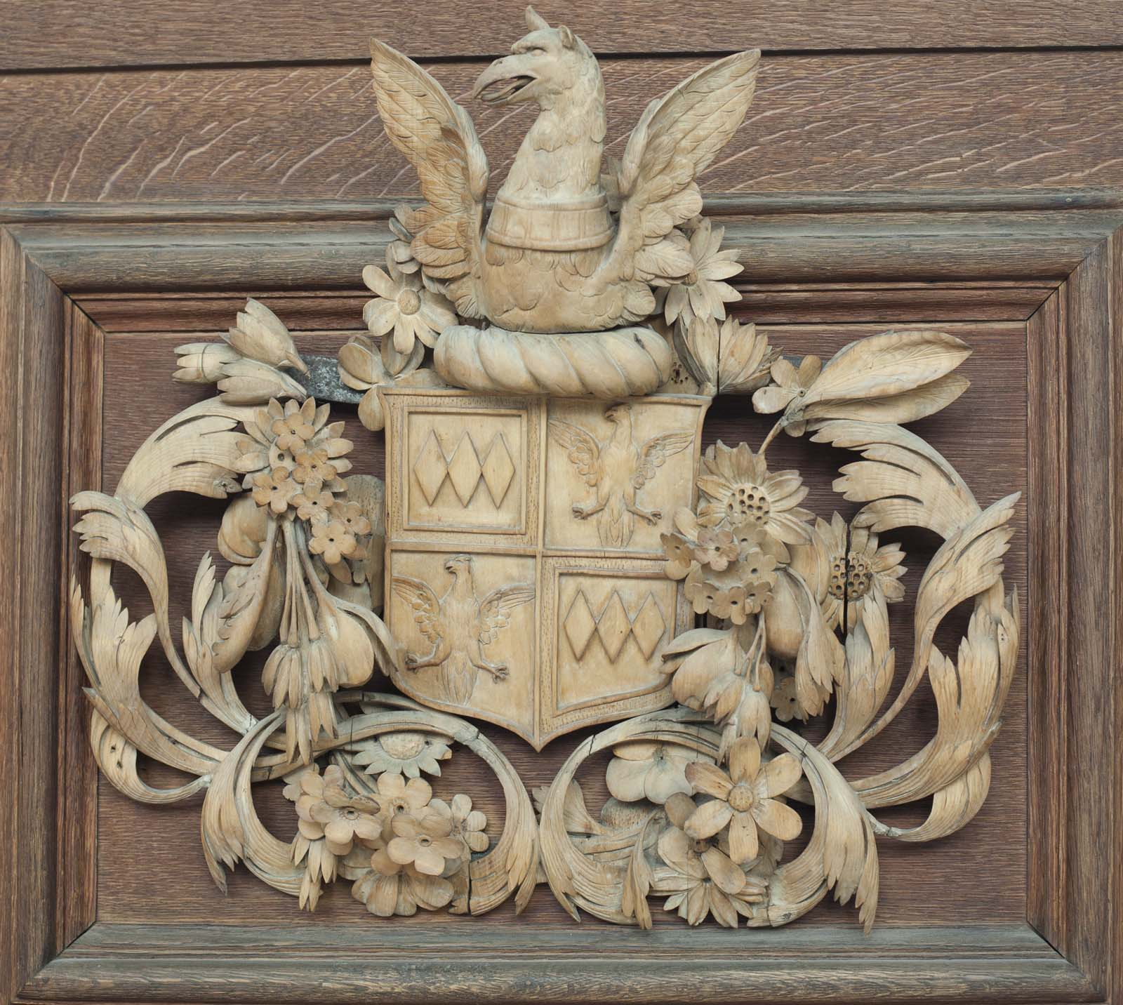 carved coat of arms with shield topped with a unicorn and flanked with foliage