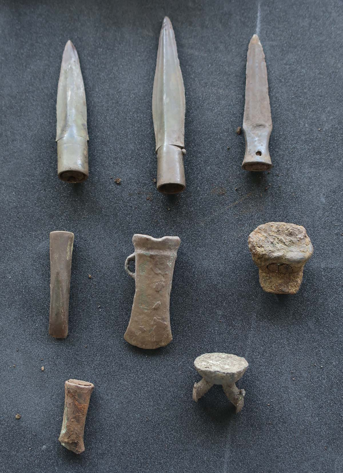 photo of laid out axe heads and spear tips