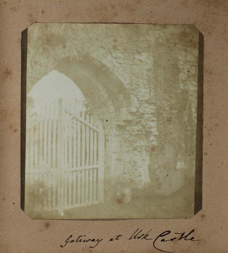faded photograph of a Gothic stone archway and gate