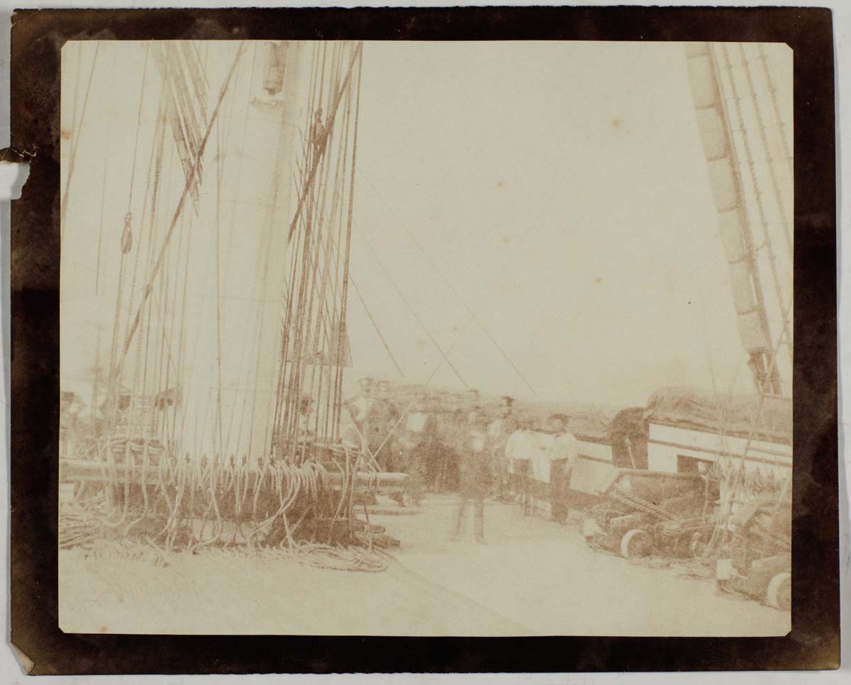 faded sepia photo of a deck of a sailing ship with cannons and sailors