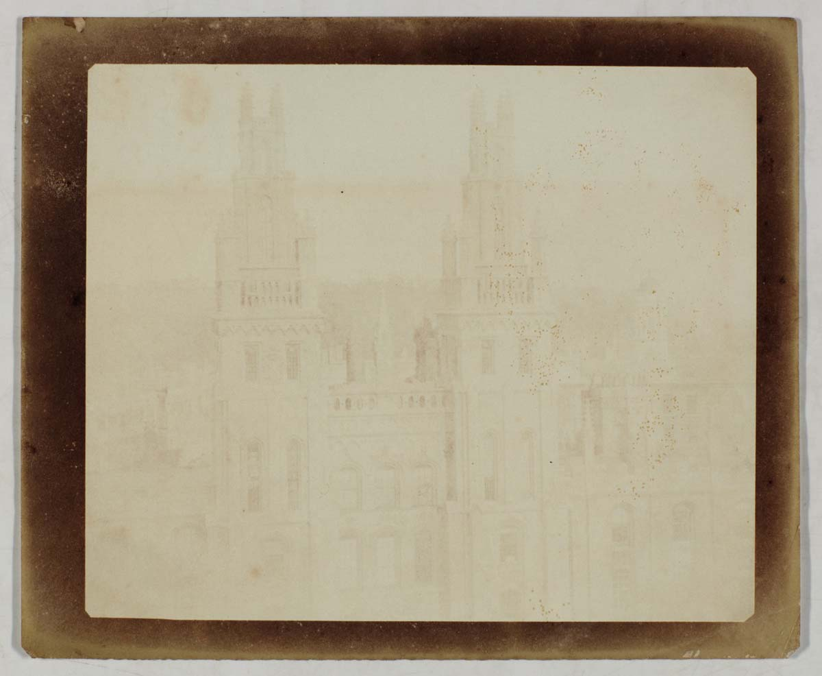 a very faded photograph of college buildings with spires at Oxford
