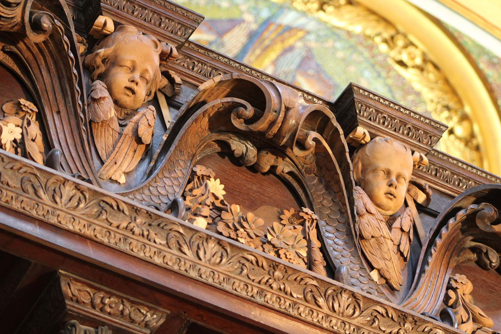 close up of wooden carved scroll work with cherubic faces and foliage
