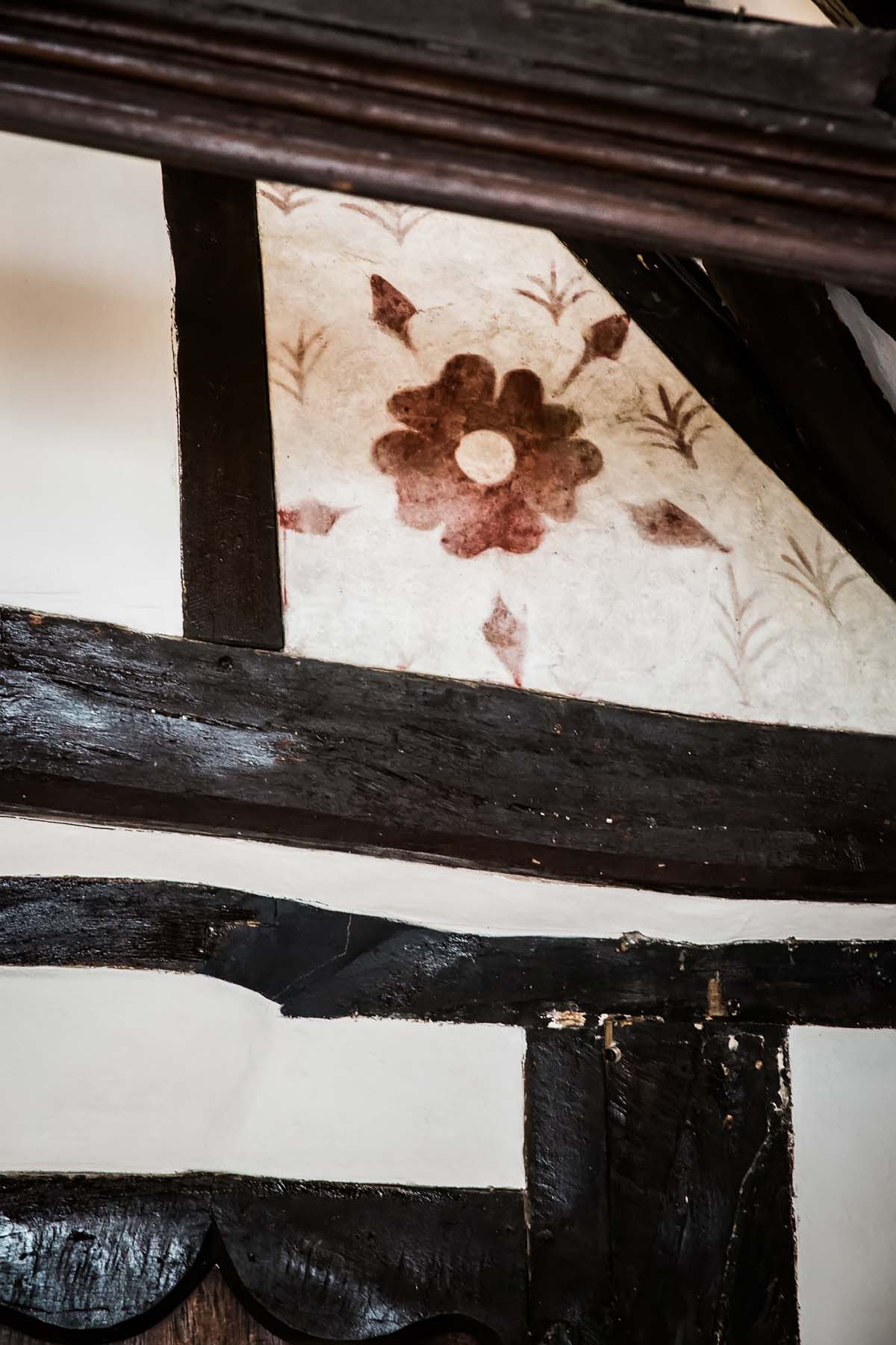 photo of a Tudor Rose painted onto a corner wall panel in a Tudor beamed room interior