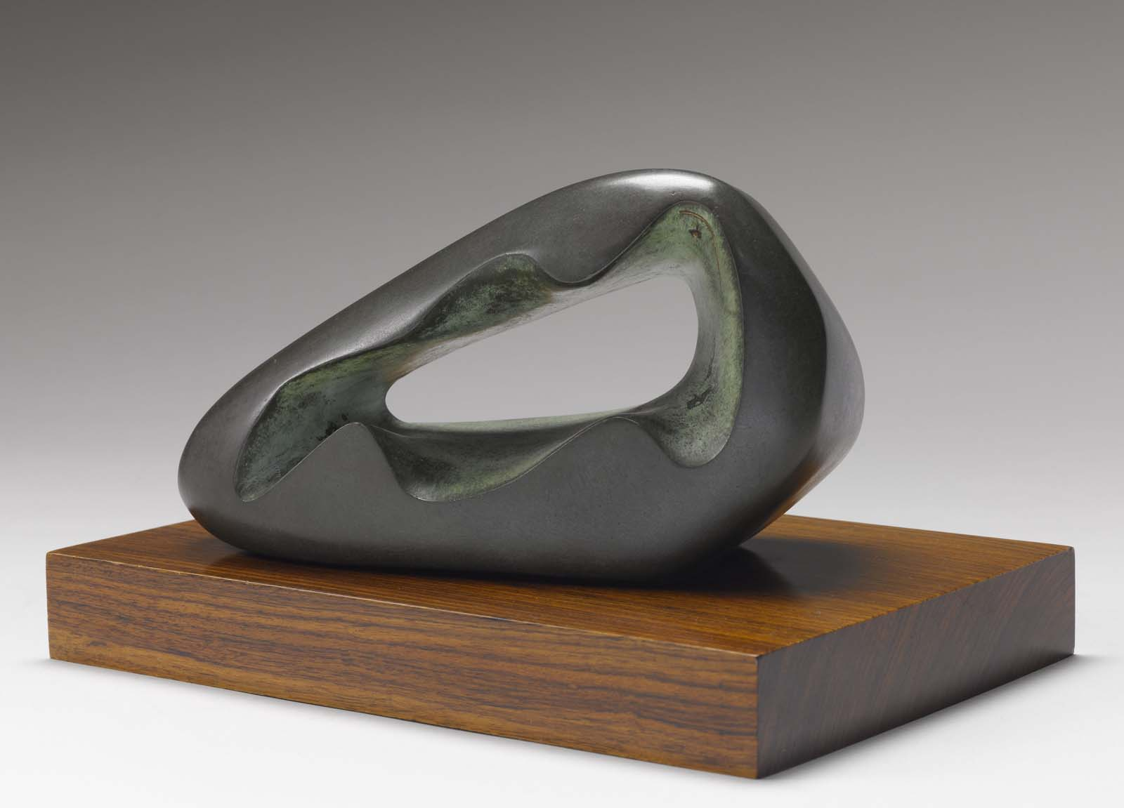 photo of an abstract bronze sculpture with central hole