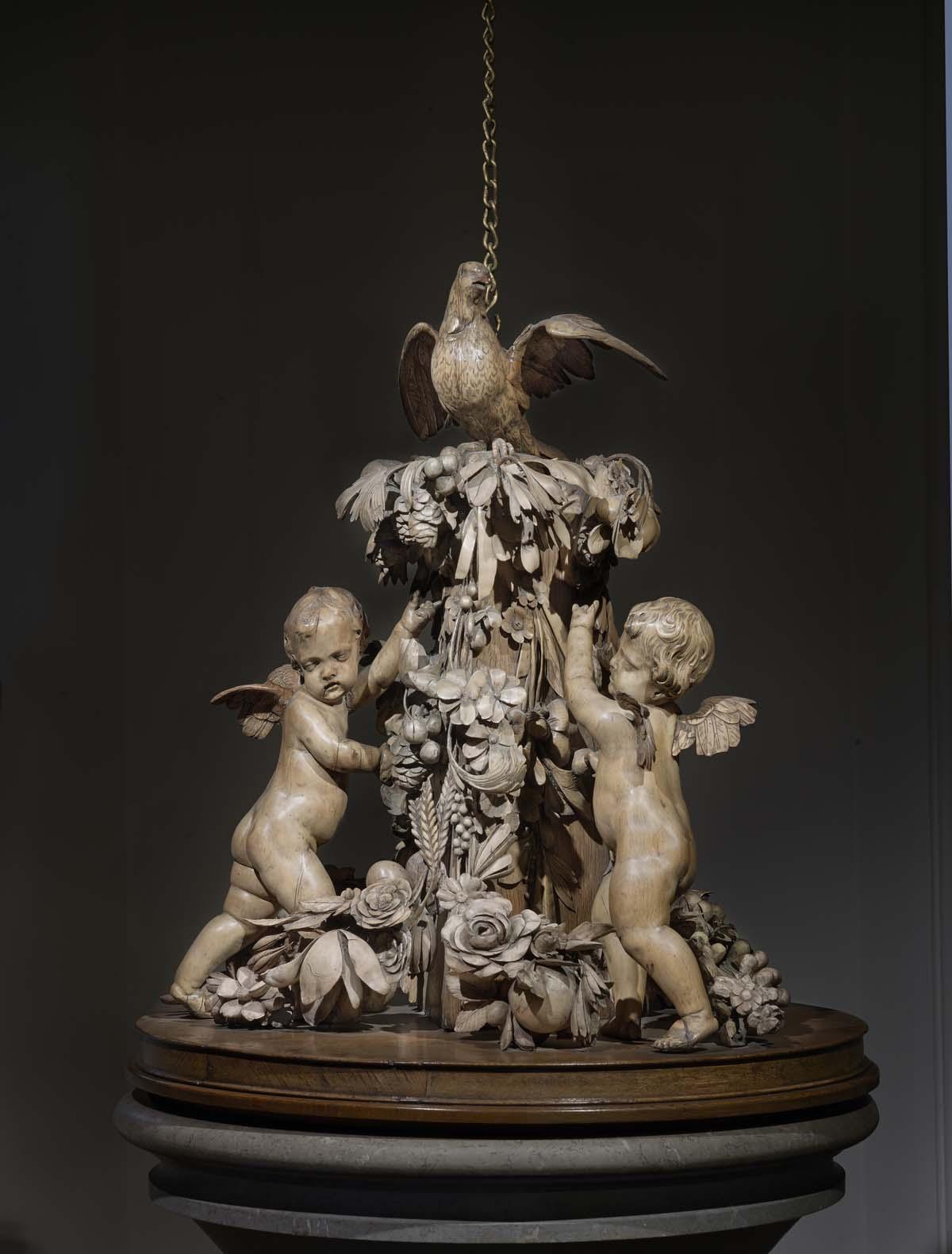 an ornate wooden sculpture of cherubs and flowers and a bird