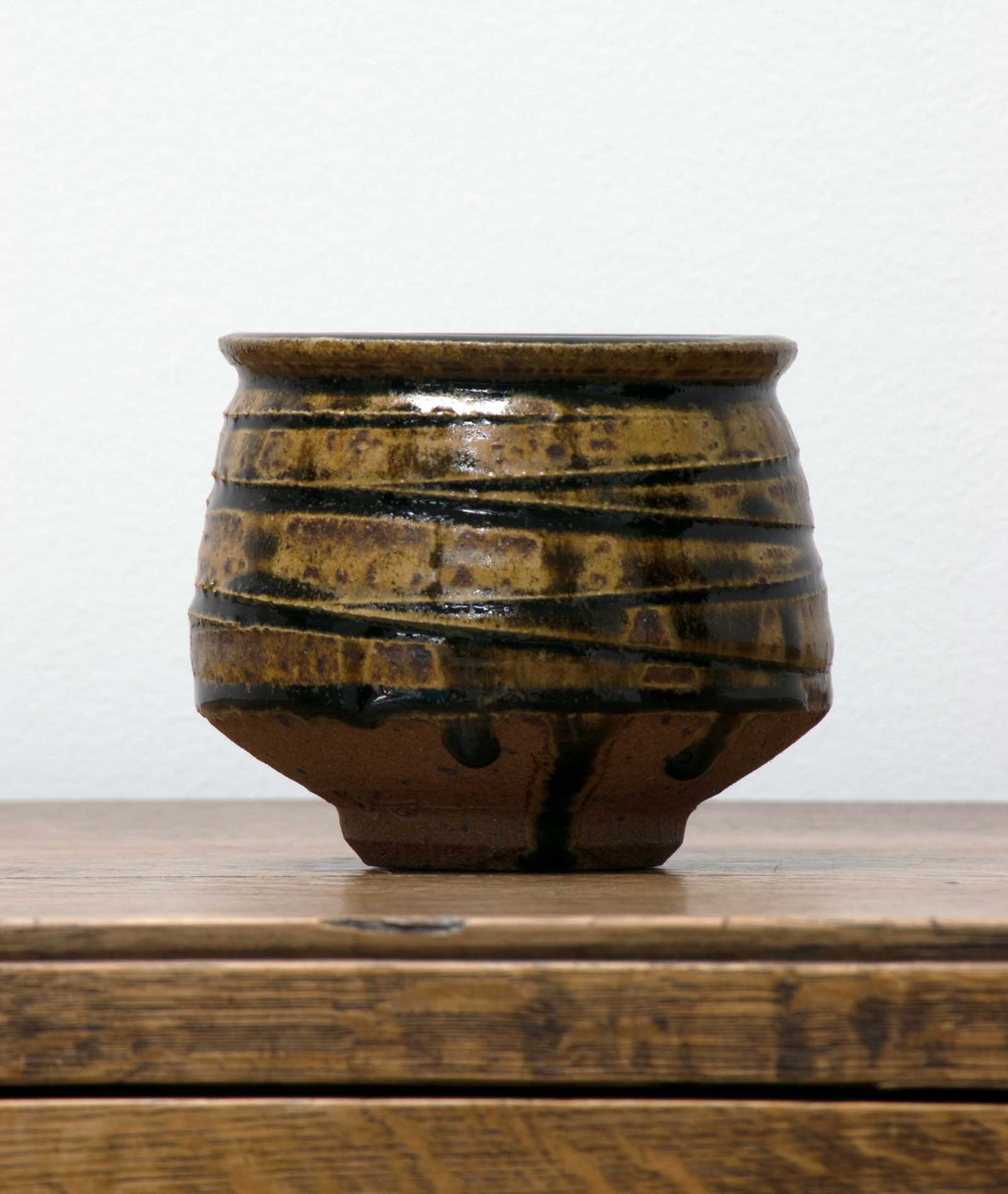 photo of a small squat bowl with a brown and green glaze