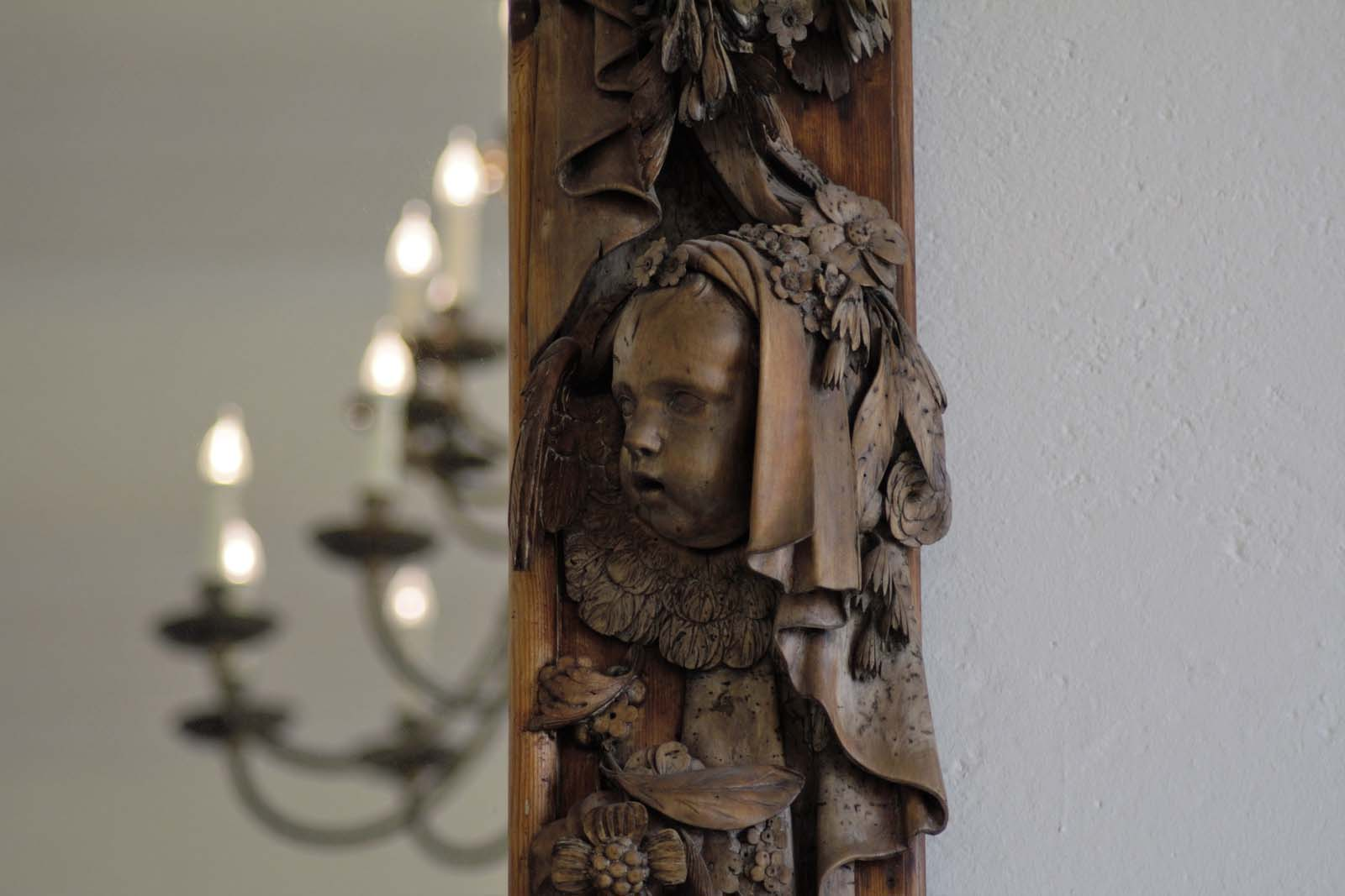 photo of a carved wooden cherub on a wood panel
