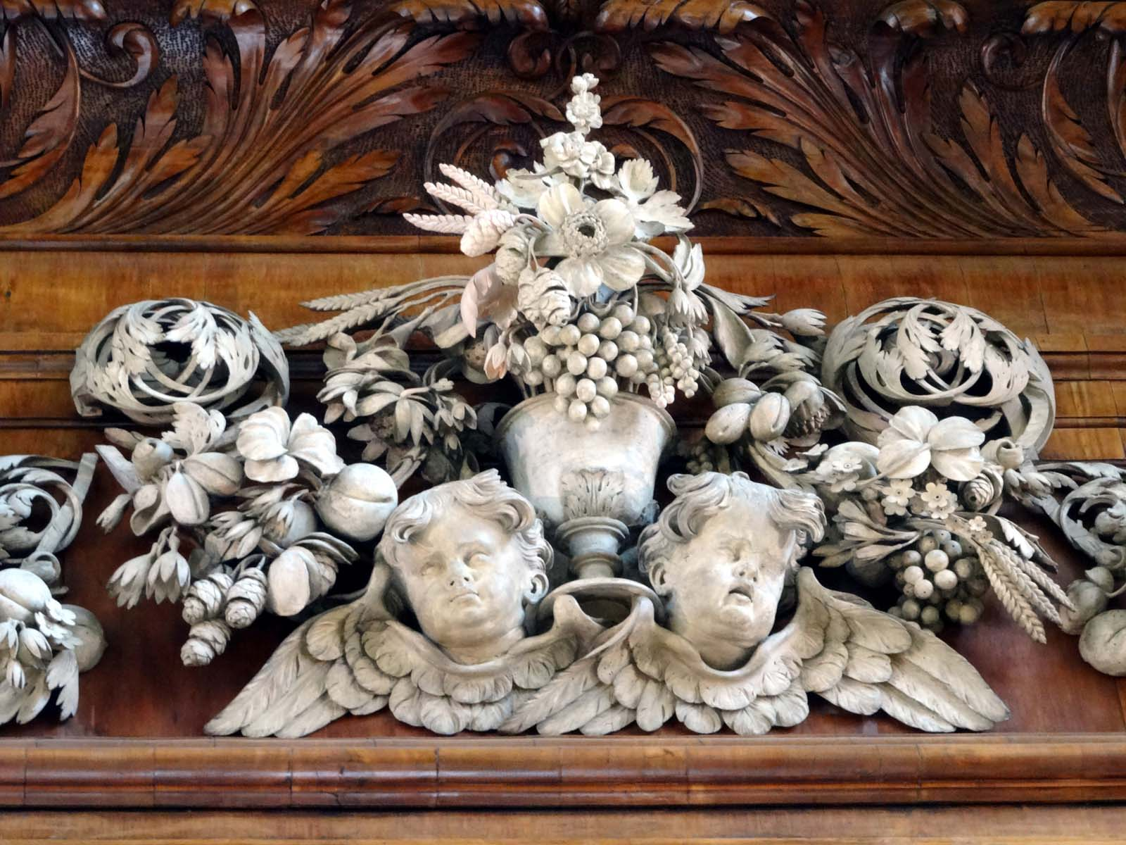 carved wooden cherubs surrounded by fruit and foliage