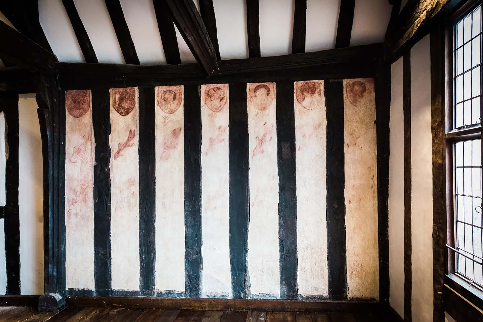 photo of a tudor period wall with beams, limewash and the remanants of portraits and roundels visible