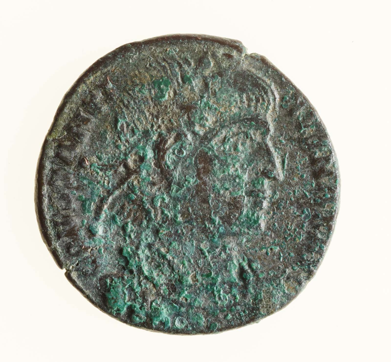 photo of a coin with roman head and verdigris
