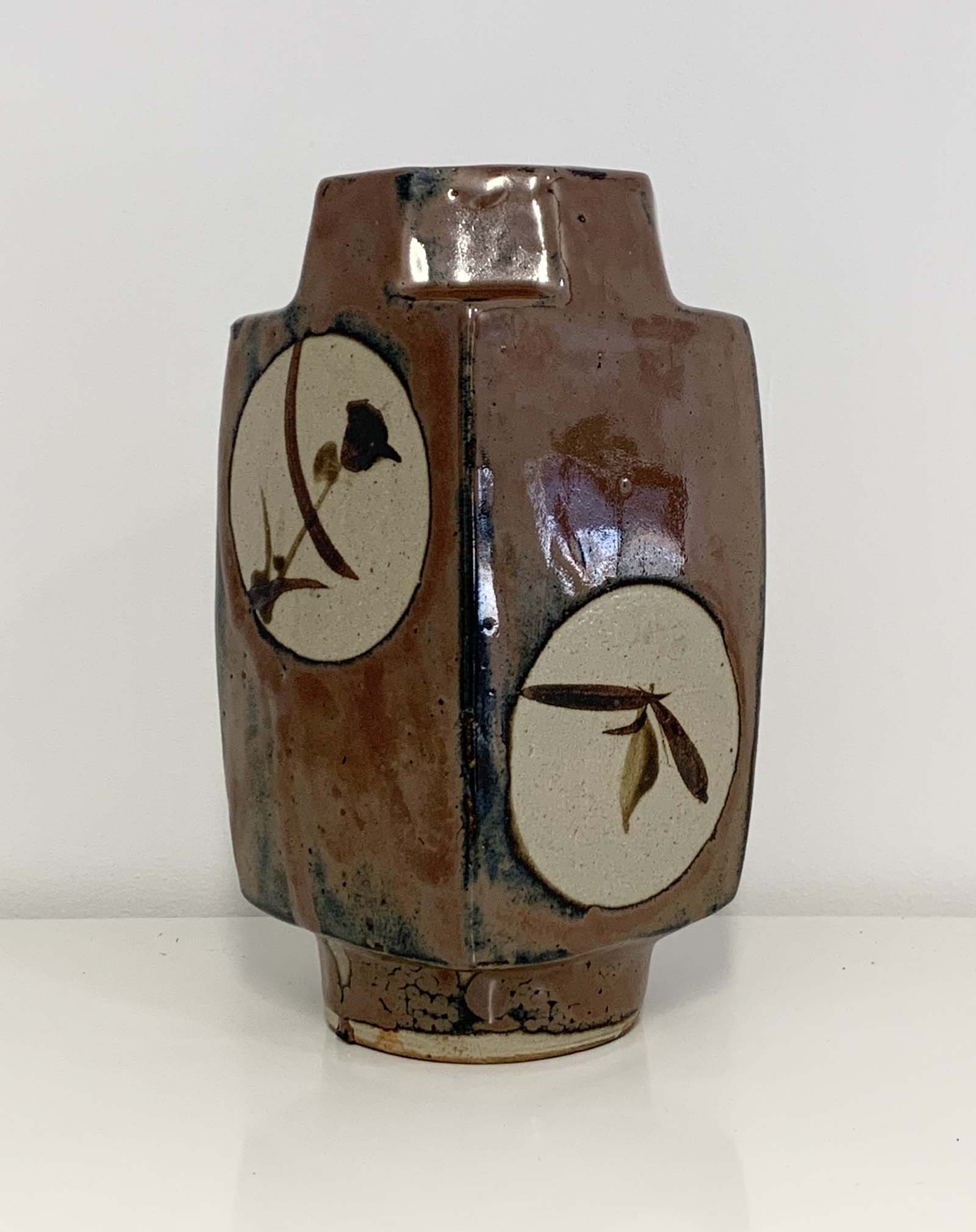 photo of a squared brown stoneware vase with circular japanese flower motifs