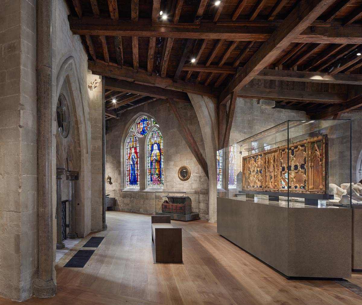 gallery view of a room with stained glass windows, stone walls and beamed ceiling with display cases