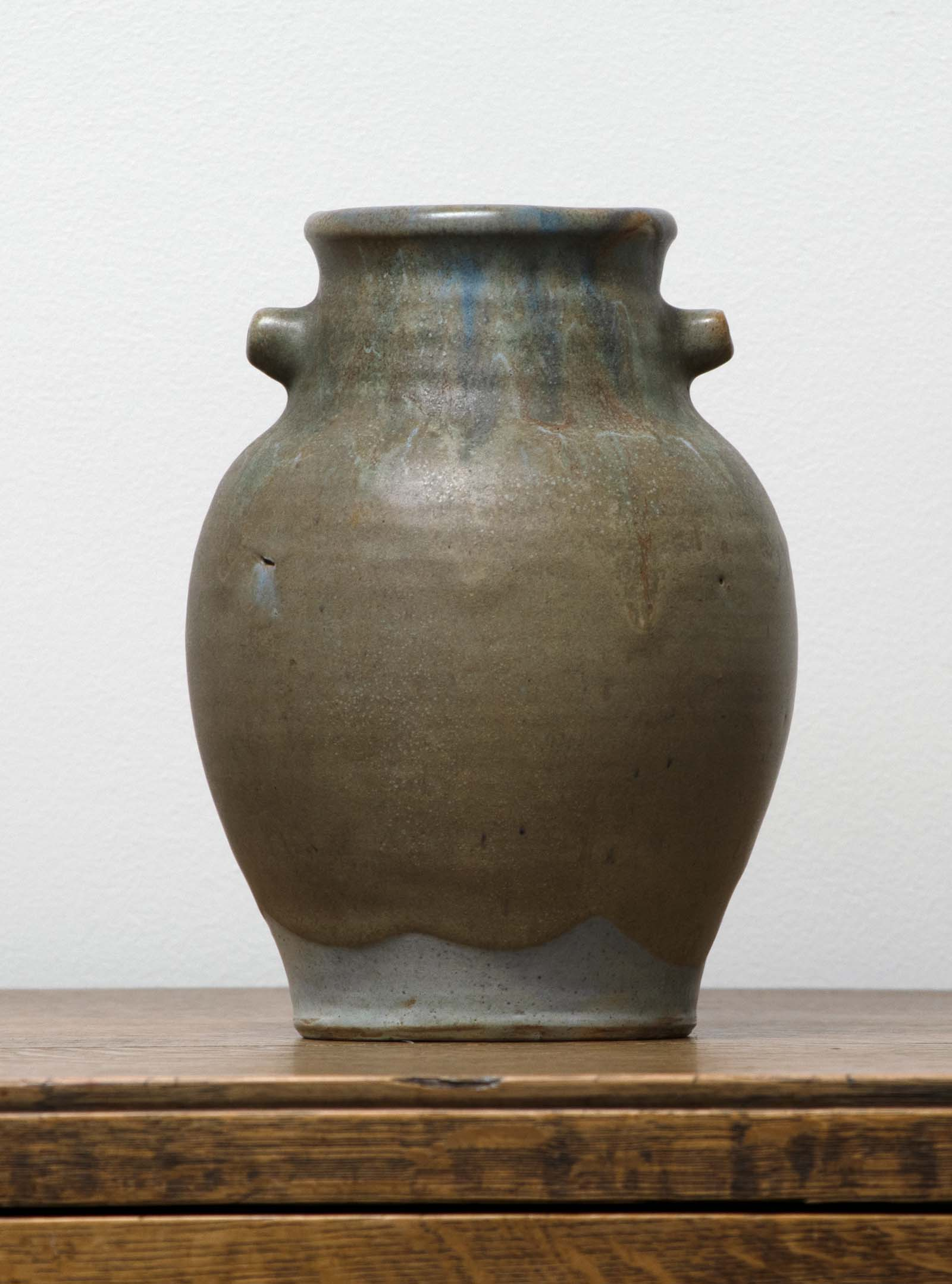 green stoneware vase with small handles by its mouthlid