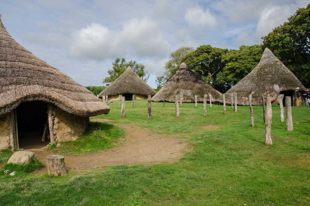 four mud huts with large conical thatched roofs set in countryside