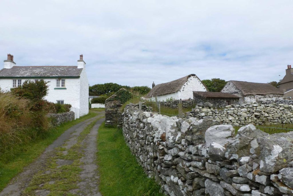 view of rural village with dry stone walls and whitewashed cottages