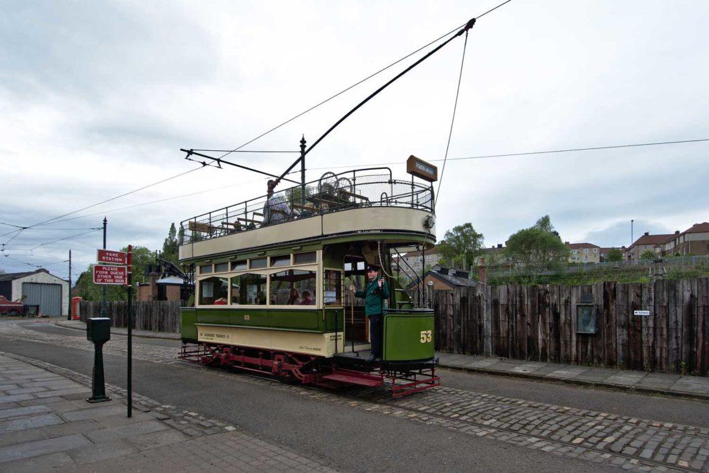 a green and cream coloured double decker tram