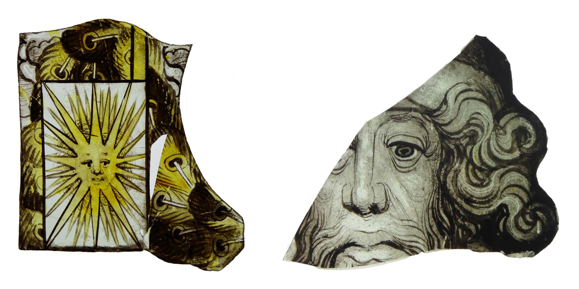 two medieval glass fragments, one showing a male face and another a sun face