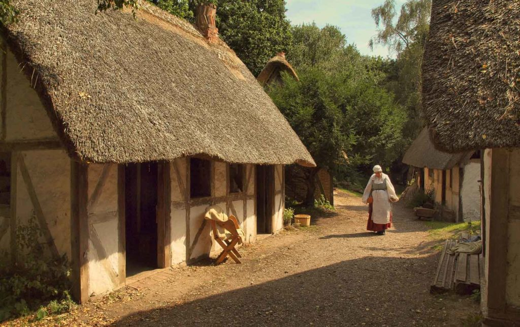 17th century style thatched buildings lining a dirt track with woman in historical dress