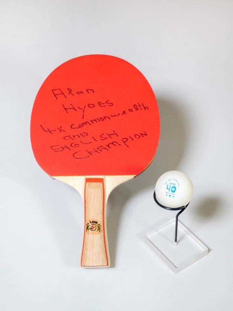 photo of a red table tennis bat and ball