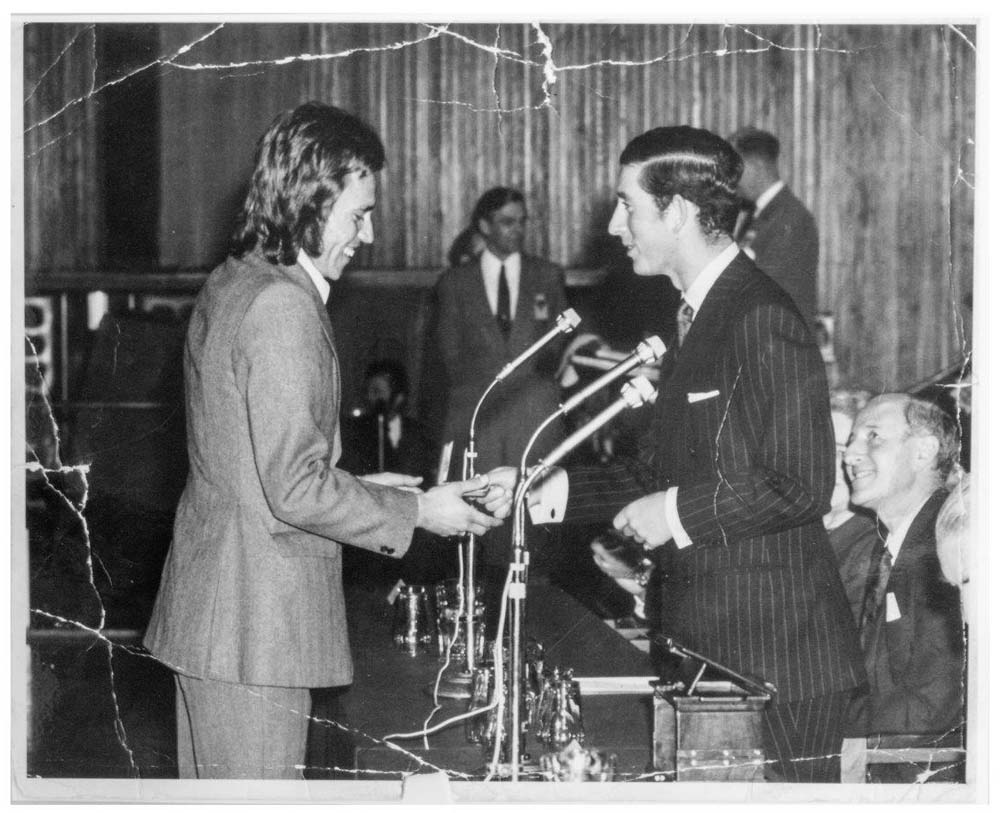 black and white photo of a man in a suit and a 1970s haircut meeting a young Prince Charles