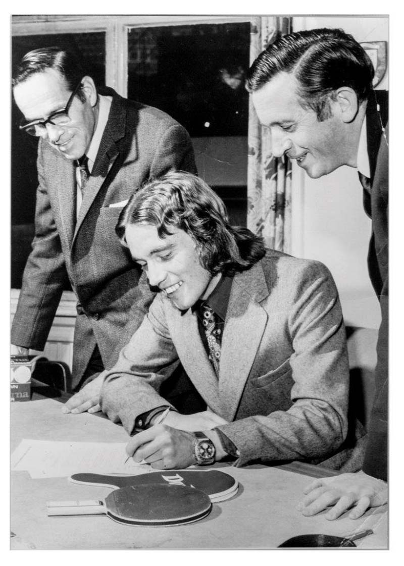 black hwote photograph of a young man with long hair wearing a suit signing something at a desk flanked by two smiling men