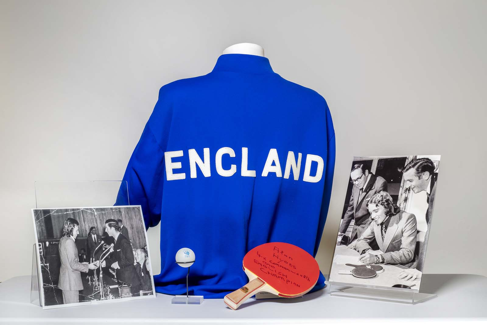 photo of a blue England track suit top flanked by a table tennis bat, ping pong ball and tow black and white photos