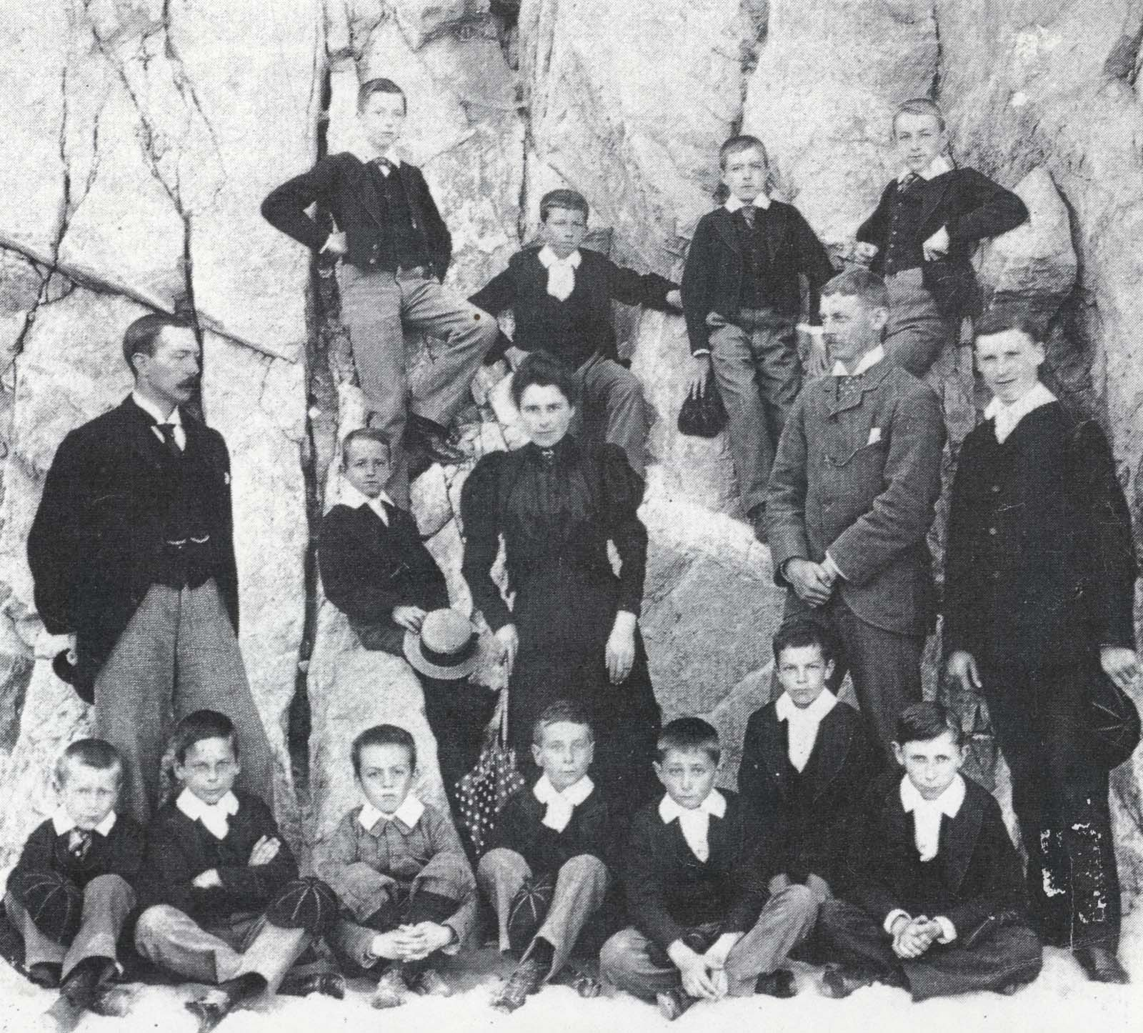 black and white school group photo of boys on a beach at the foot of cliffs with teachers