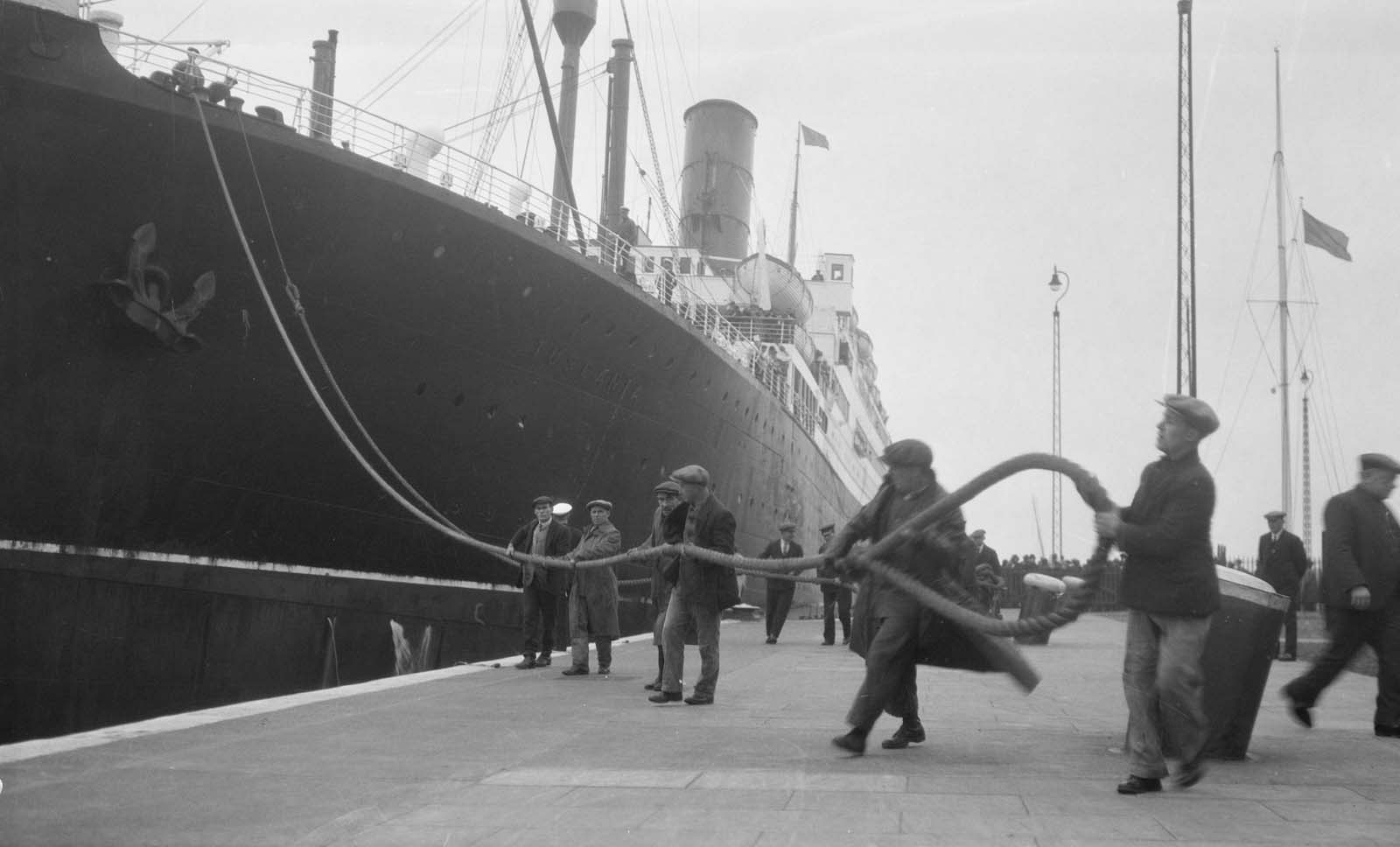black and white photo of dock workers hauling the rope of a liner