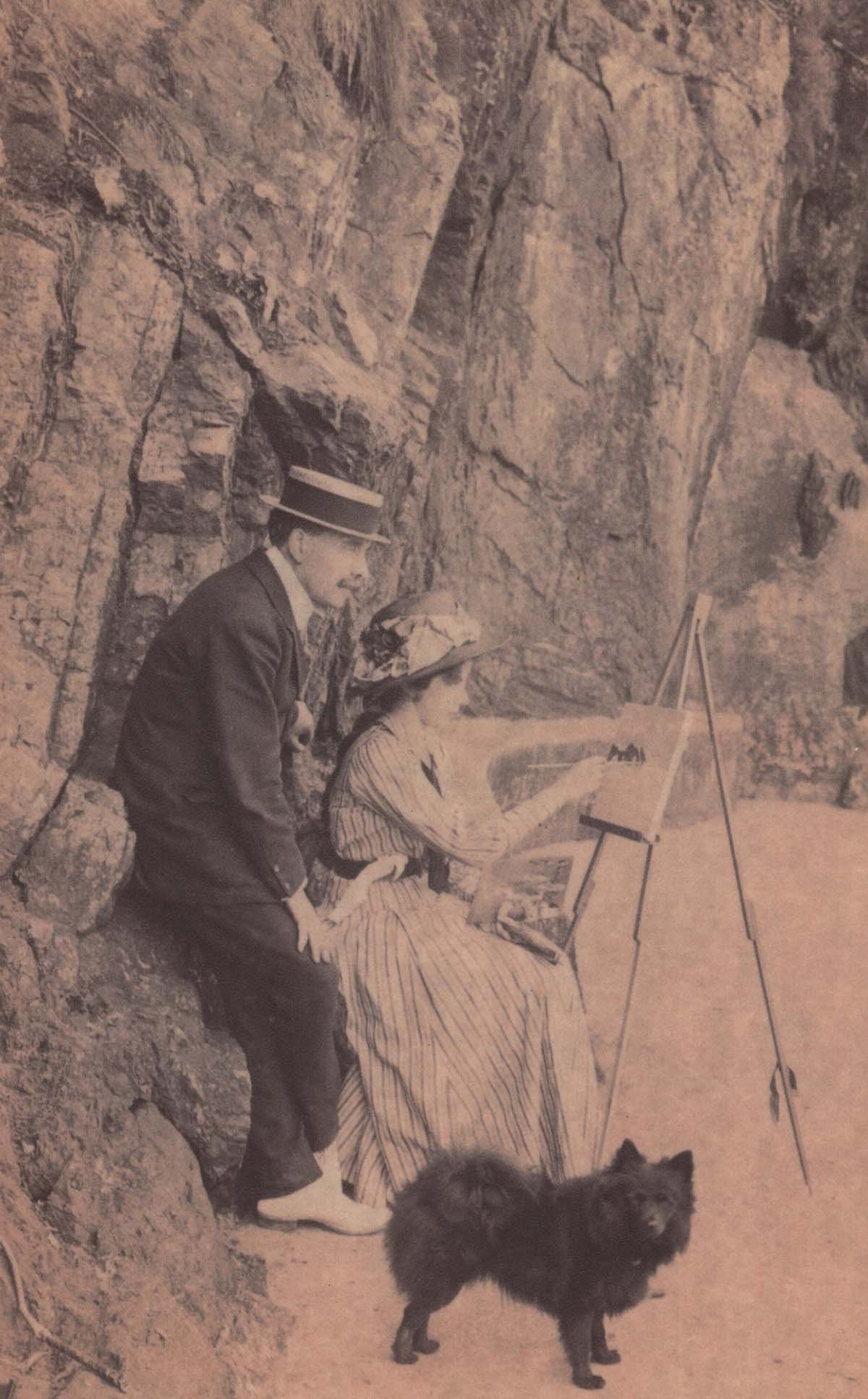 black and white photo of and Edwardian man in straw boater perching on a rock on beach as a young woman paints on an easel before him