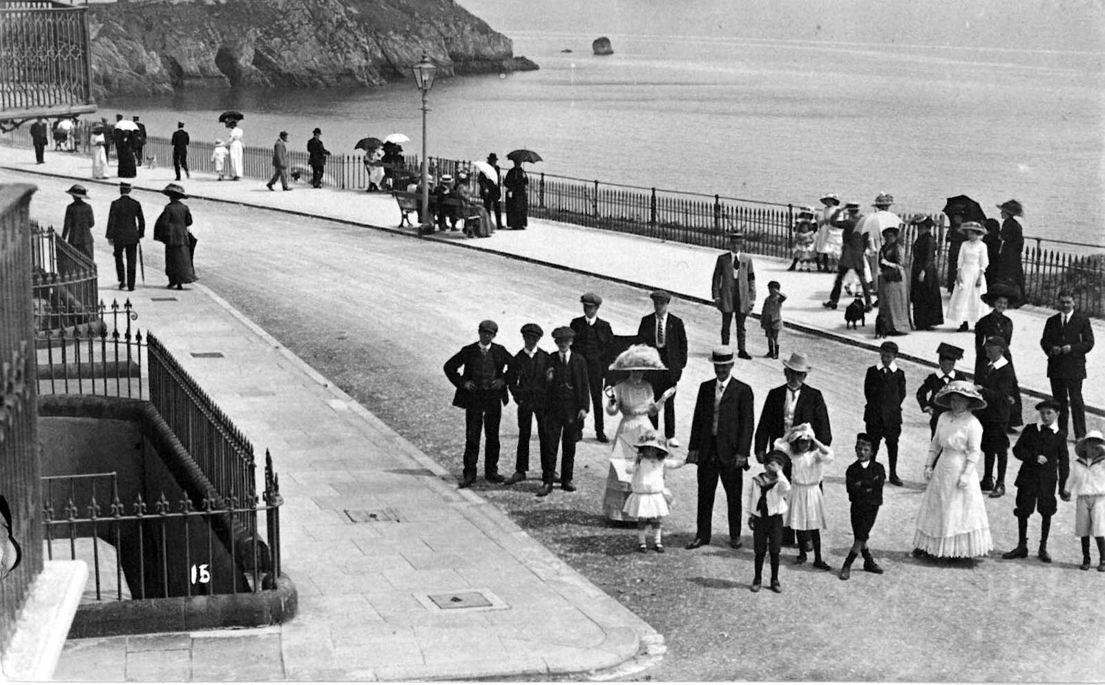 photo of people on a coastal esplanade in their Edwardian Sunday best with the sea beyond them