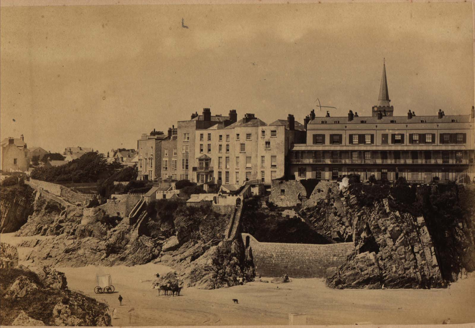 black and white photo of large houses along an esplanade above a clifftop seen from a beach