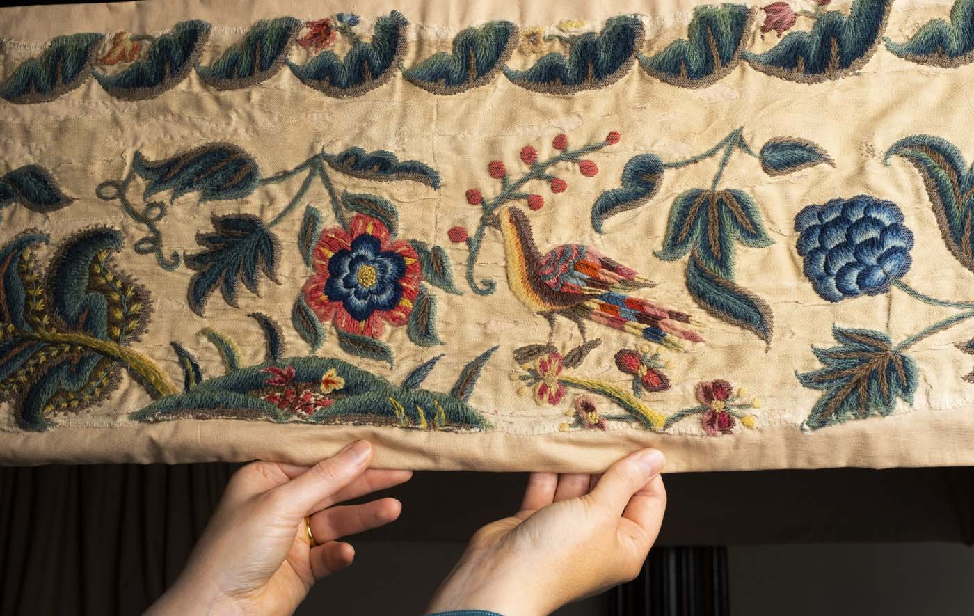 detail of an embroidered piece of cloth with bird and flower designs