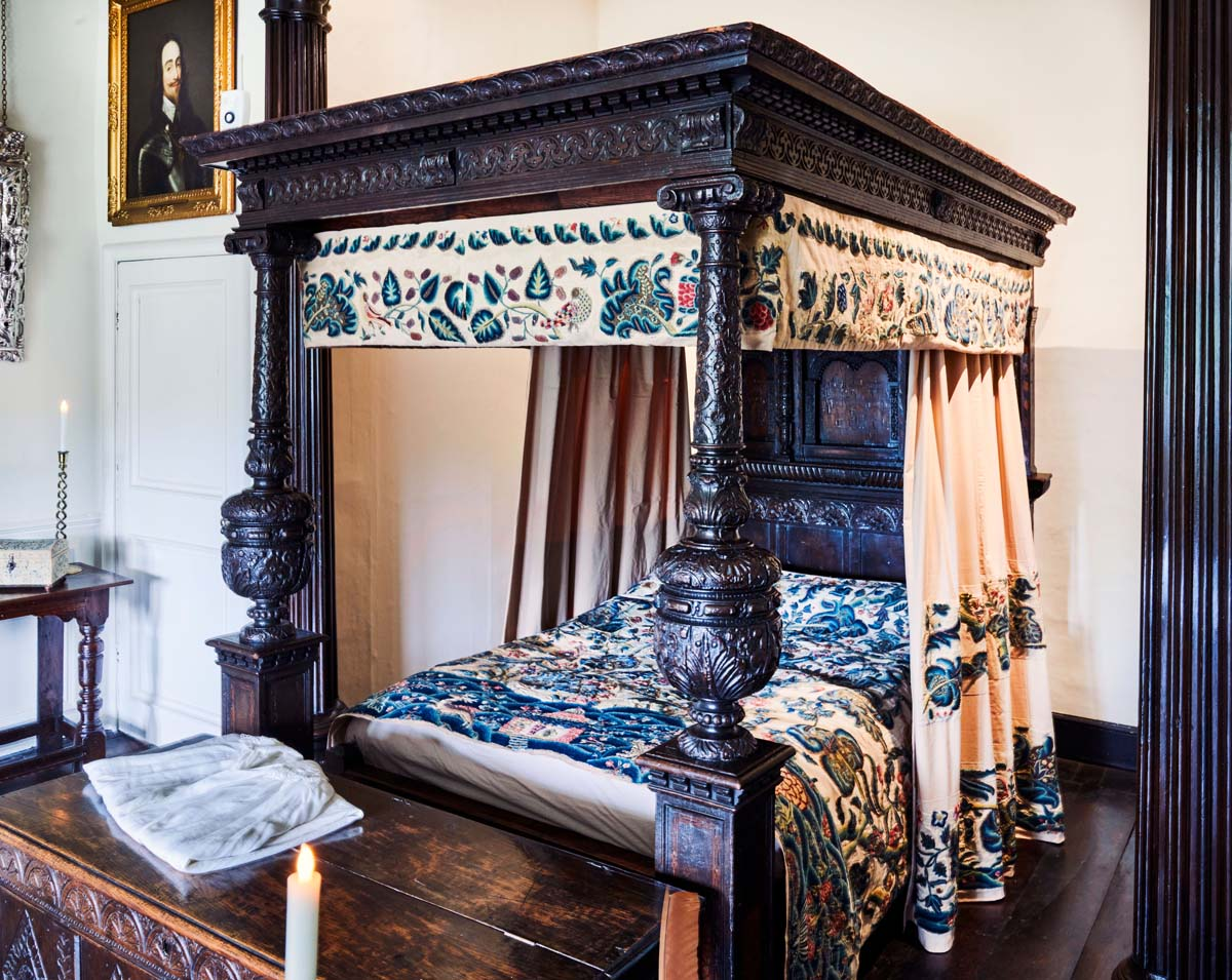 photo of a four poster bed decorated with embroidered coverings and a pelmet