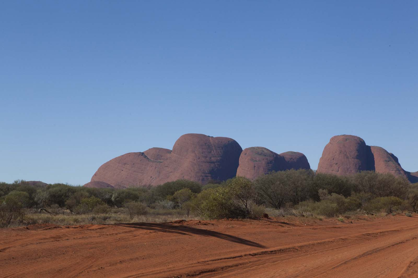 photo of a series of red sandstone rocks emerging from an arid landscape framed by a blue sky