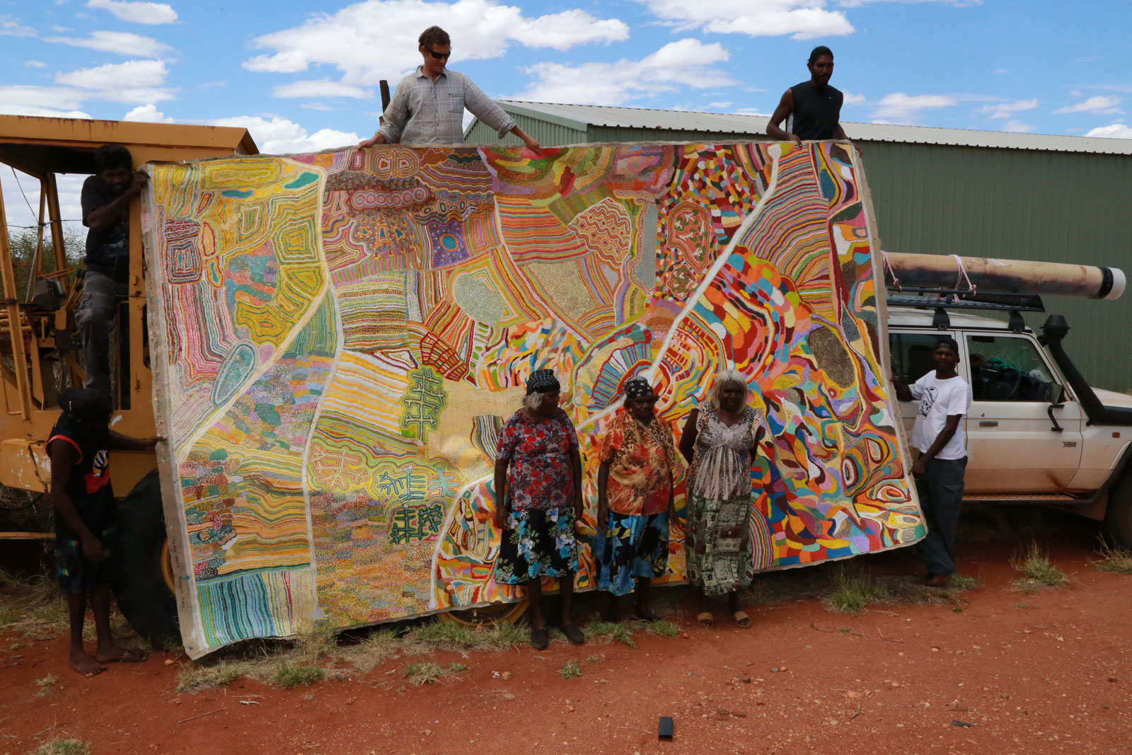 photo of various people outside next to a huge canvas of abstract shapes and lines in many colours