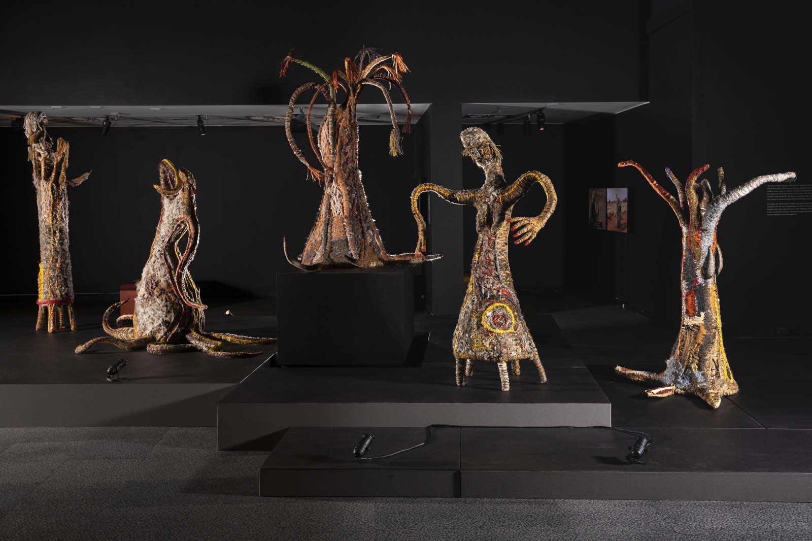 installaton shot of several sculptural figures represnting women made from natural fibres and plant materials