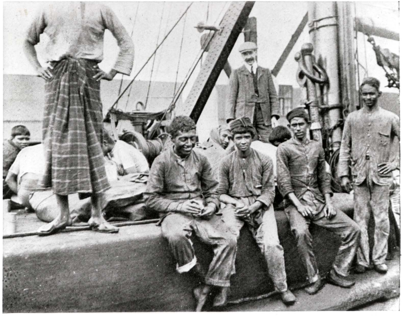 photo of a group of seamen siting on the deck of ship