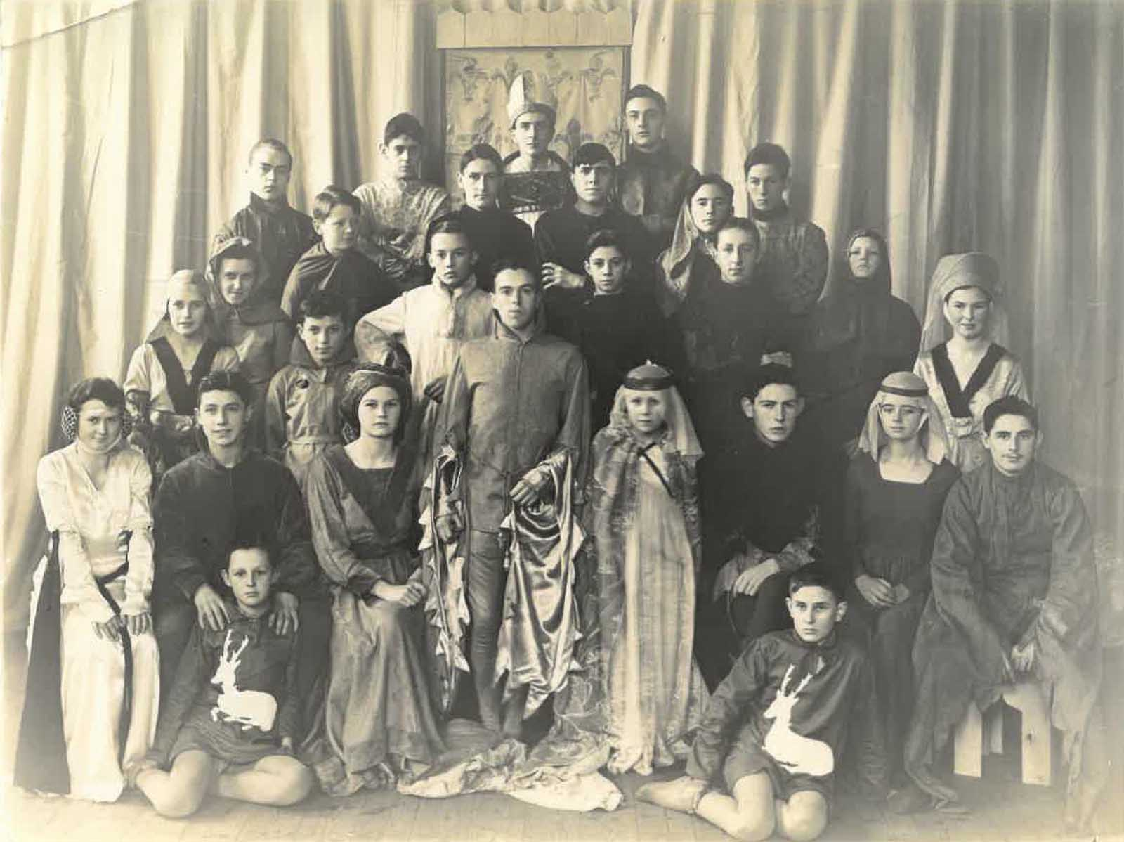 a black and white group photo of the cats of theatre production with women, children and men in medieval attire