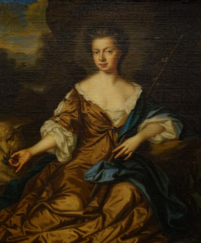 portrait of a seated woman with her hand feeding a sheep