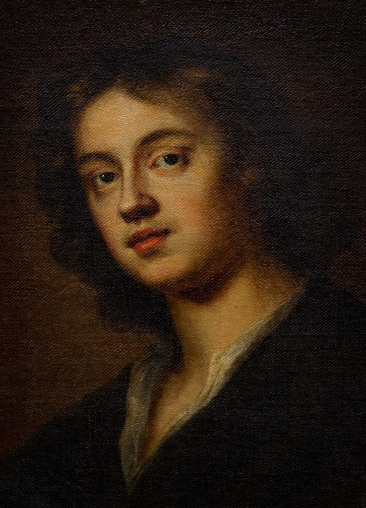 head and shoulders portrait of a young man with shoulder length hair