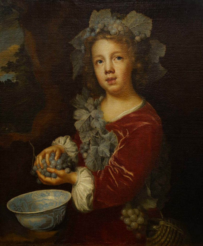 portrait of boy with laurel wreath cradling a bunch of grapes