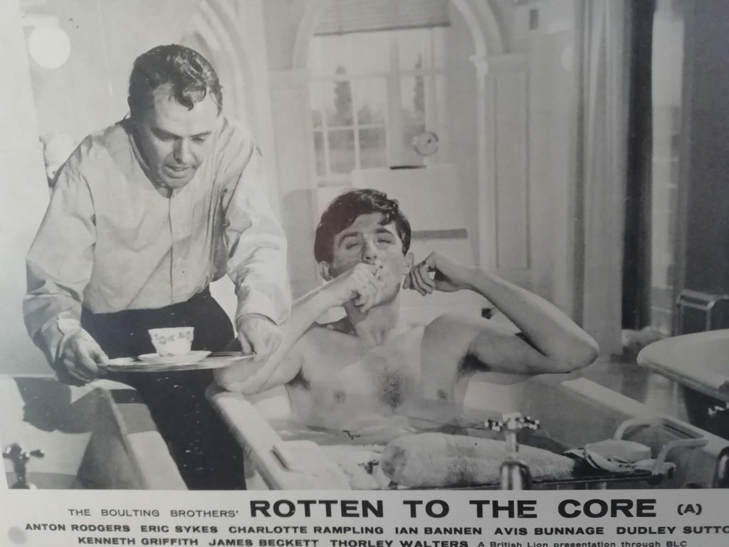 a front of house still for a film scene with a man in a bath smoking a cigarette being served a cup of tea by another man