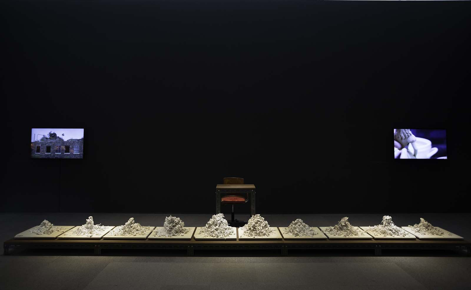 photo of a darkened room with piles of ceramic fragments lined across a table