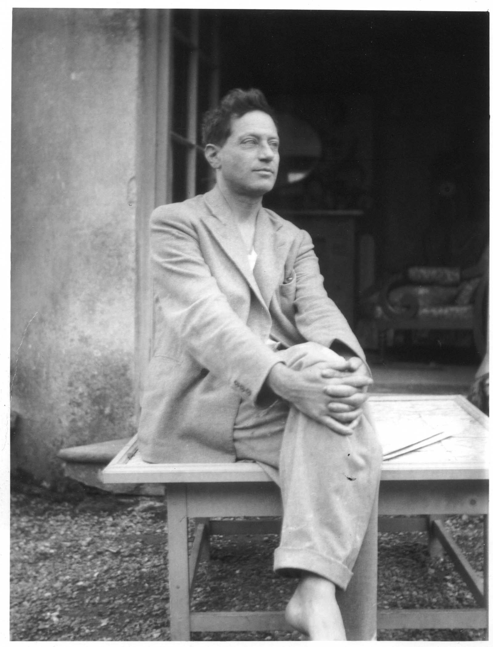 black and white photo of a man in a linenen suit with his hands clasped across his crossed legs
